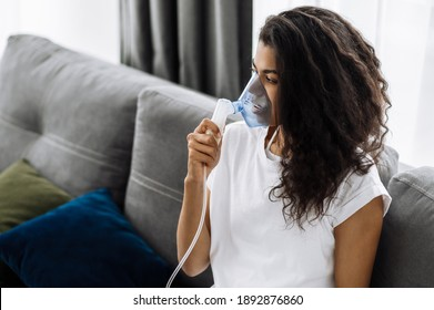 Close-up photo of sick african american woman with an inhaler. Unhealthy millennial girl doing inhalation at home, she use nebulizer and inhaler for the treatment sitting on the couch at home at