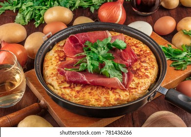 A closeup photo of a Spanish tortilla in a traditional tortillera, with jamon and parsley