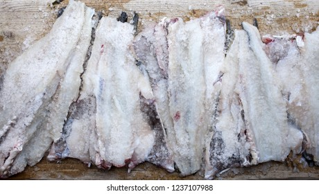 Closeup photo of splitted and heavily salted raw cod - traditional method for preservation of fish in Norway. Photo of privately salted fish, not commercial process.