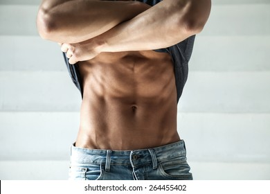 closeup photo sports guy in jeans with perfect abdominal muscles