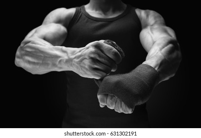 Close-up photo of strong man wrap hands on black background Man is wrapping hands with boxing wraps Strong hands and fist, ready for training and active exercise