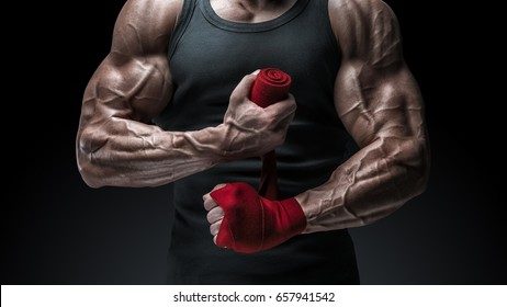 Close-up photo of strong man wrap hands Strong hands and fist, ready for training and active exercise Man is wrapping hands with red boxing wraps isolated on black background