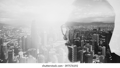 Closeup photo of stylish bearded banker wearing glasses and looking city. Double exposure, panoramic view contemporary megalopolis background. Space for your business message. Wide, black white.