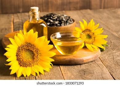 Photo en gros plan d'huile de tournesol avec graines sur fond bois. Concept bio et produit biologique.