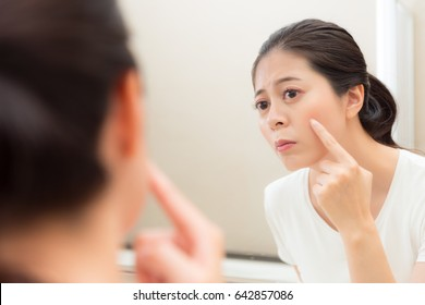 closeup photo of sweet beautiful female model looking at mirror found cheek having acne sadness use finger to touch illness position in bathroom.