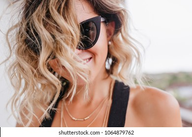 Close-up photo of tanned woman with trendy haircut. Portrait of laughing female model posing on sky background in sunglasses.