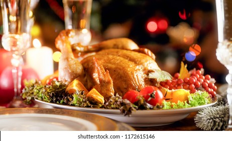 Closeup photo of tasty baked chicken against glowing Christmas tree with colorful lights