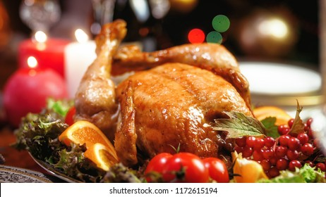 Closeup photo of tasty baked chicken against glowing Christmas lights and burning candles