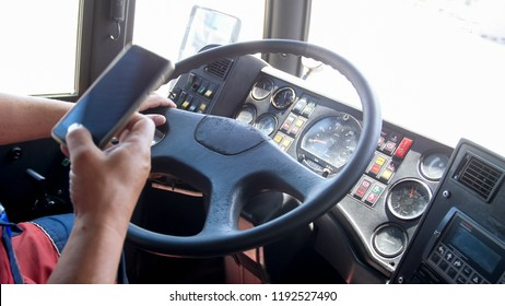 Closeup photo of truck driver using smartphone while driving. Danger in transport. Irresponsible driver
