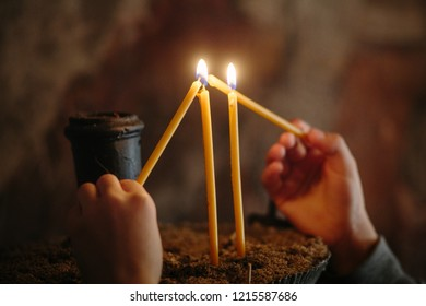 Close-up photo of two child hands lighting candles in church.