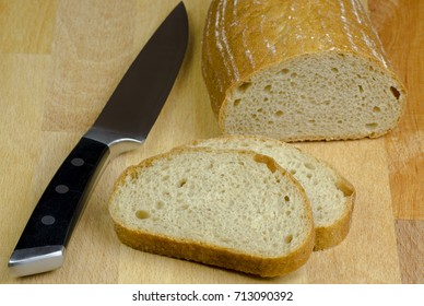 Close-up photo of two slices of bread cut by knife with black handle on a wooden board table with blurred background