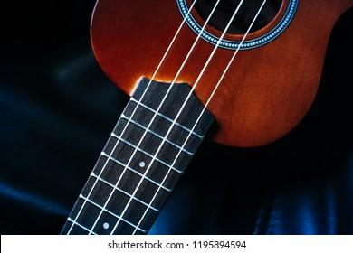 closeup photo of a ukulele against a black leather background