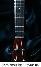 closeup photo of a ukulele neck against a dark background