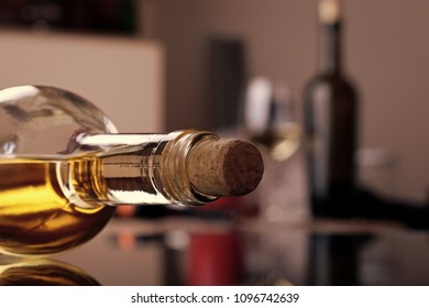 Closeup photo of uncorked bottle of aromatic sweet golden amber color white wine lies on table and another bottle of wine with filled glass on background in kitchen, horizontal picture.