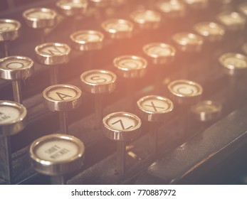 Closeup photo of vintage black grunge typewriter machine has antique alphabet with sunlight , selective focus. Vintage color tone Closeup Photo.