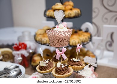 Close-up photo of wedding cupcakes placed on a glass stand on a dessert table at wedding reception, pink-brown color palette