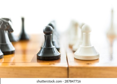 Closeup photo of white and black pawns standing in front of each other on wooden board