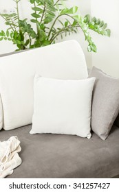 Closeup photo of white decorative cushion lying on gray sofa at living room