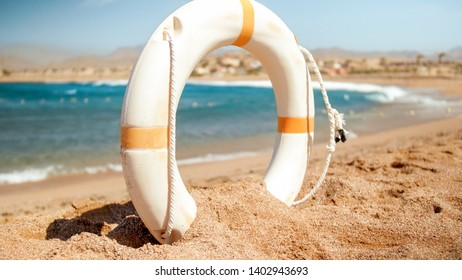 Closeup photo of white plastic life saving ring on the sea beach at bright sunny day. Perfect shot to illustrate summer holiday vacation at ocean.