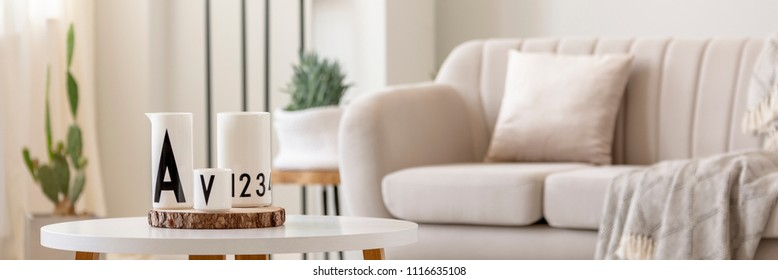 Close-up photo of white vessels standing on white end table in bright living room interior with sofa and plants in blurred background