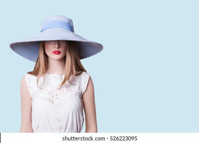 Close-up Photo Woman in Blue Slag on her Face, Beautiful Photography in Studio. Beautiful Girl with hat Posing in Studio. Sexy Girl Photography in Hat and Red Lips.   Isolated on Blue Background
