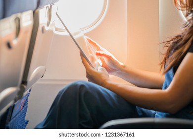 Closeup photo of Woman hands using a tablet inside an airplane.