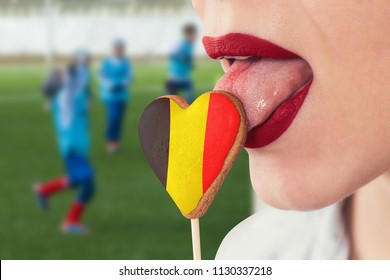 Closeup photo of the woman lips and cookie hearts with flag of Belgium