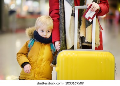 Close-up photo of woman with little boy at the international airport. Mother holding hands with her cute little son. Family travel or immigration concept