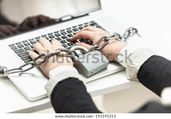 Closeup photo of woman locked in chain typing on laptop