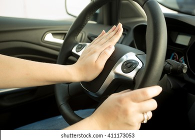 Closeup photo of woman pressing honk button on steering wheel