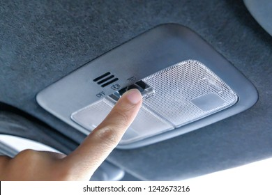 Closeup photo of woman turning light on in car salon. Open hand lamp in car.