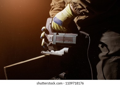 Closeup photo of a worker in outfit with blue gloves using electrical jigsaw side view on black background with upper light.