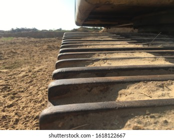 a closeup photo of a worn out caterpillar track with sand stuck between the ribs.