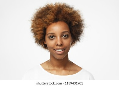 Closeup photo of young african american woman isolated on gray background, dressed in white t shirt, smiling cheerfully