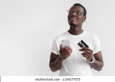 Closeup photo of young African male in eyeglasses pictured isolated on gray background thinking and dreaming about pleasant plans with credit card and smartphone in hands, ready to purchase in web