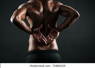 Close-up photo of young african sports man feeling pain in his back, isolated on black background