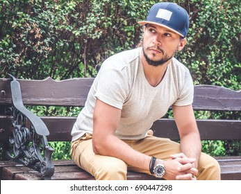 Closeup photo of Young Bearded Man sitting on bench in gray t-shirt and Blue Baseball Cap Mockup