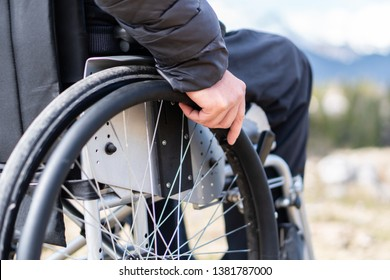 Closeup photo of Young disabled man holding wheelchair outside in nature observing mountains and nature