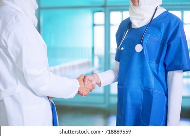 Close-up photo of young female arabic doctor and a nurse  white and blue medical uniform and a white hijab shaking hands