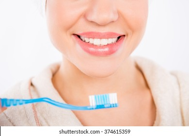 Closeup photo of young girl smiling with perfect  white teeth and toothbrush