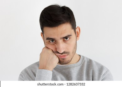 Close-up photo of young handsome man isolated on gray background, pressing hand to chin looking bored, exhausted and disappointed, feeling upset facing problems