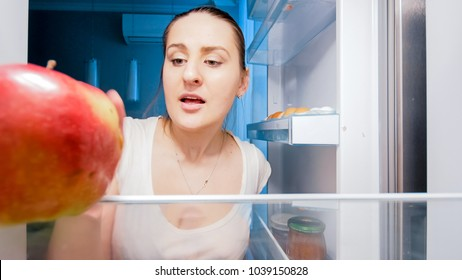 Closeup photo of young hungry woman looking for something to eat in refrigerator at night