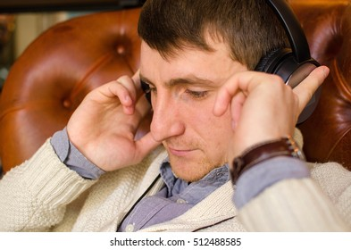 Close-up photo of young man listening music in headphones
