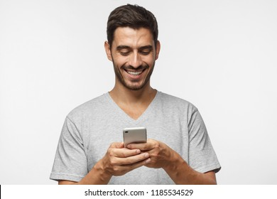 Closeup photo of young man looking at screen of smart phone, smiling nicely while chatting with friend