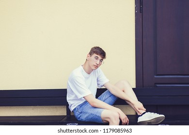 Closeup photo of young man sitting on bench in white t-shirt