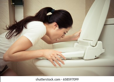 closeup photo of young pretty woman vomiting into toilet bowl when she in early stages of pregnancy feeling nausea everyday.