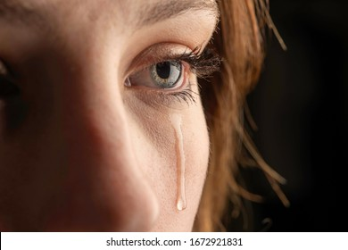 closeup photo of a young woman crying with a tear running down her cheek.