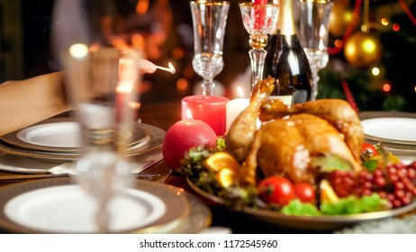 Closeup photo of young woman lighting candles of family Christmas dinner table at living room