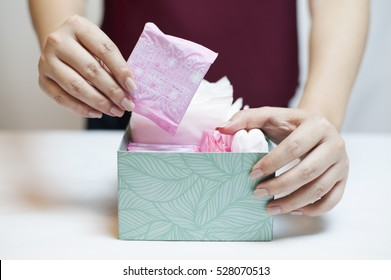 Closeup photo of young woman picking sanitary pad out of green box