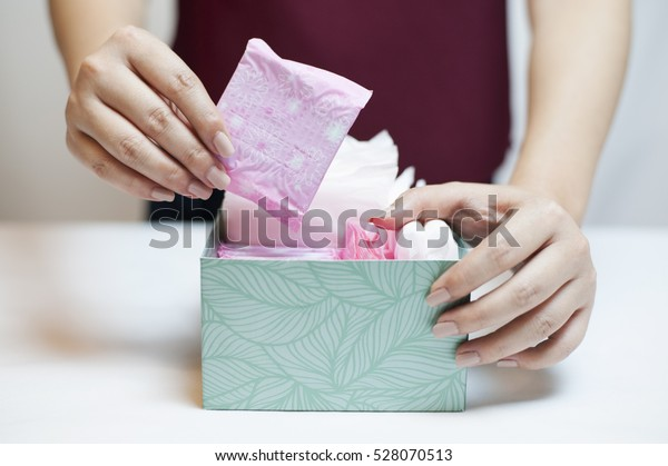 Closeup photo of young woman picking sanitary pad out of green box